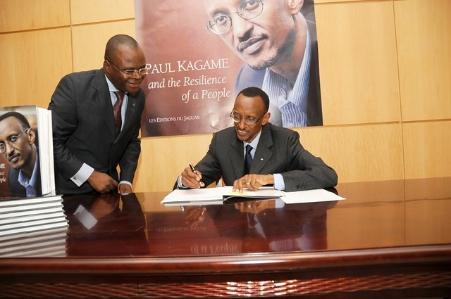President Paul Kagame signs one of his book for a fan. (flickr)