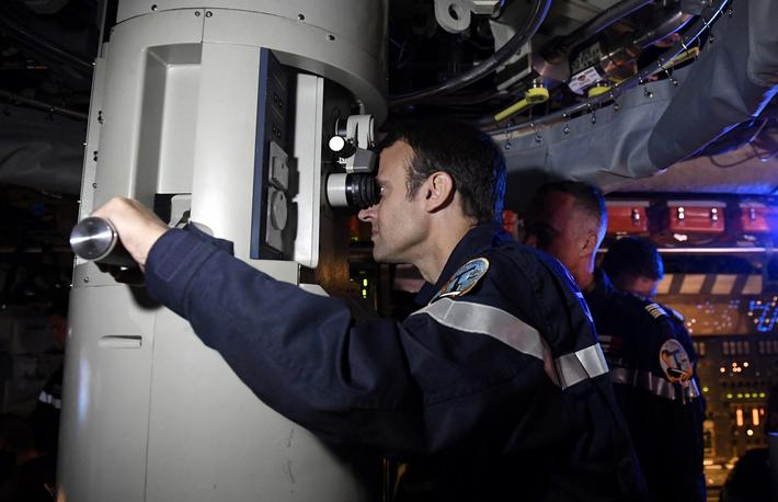 "French President Emmanuel Macron looks through the periscope of submarine ""Le Terrible"" during a vis"