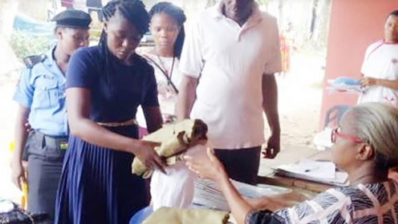 One of the two sacked female corps members returning her kits before being escorted out of the Ebonyi NYSC camp on Sunday, November 10, 2019.  (Punch)