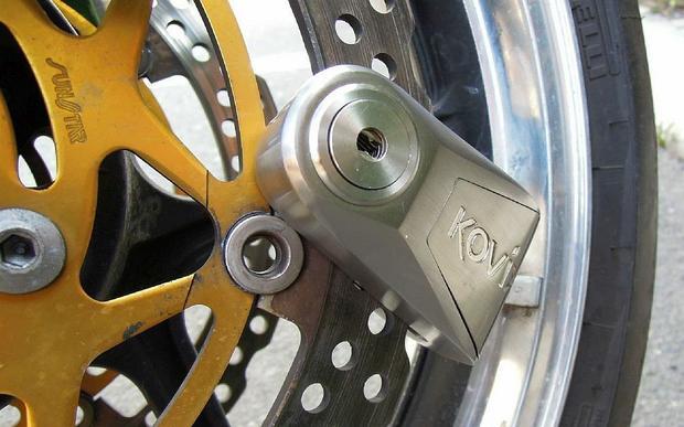 Blokada motocyklowa z alarmem Kovix KNL14 zapięta na tarczy hamulcowej