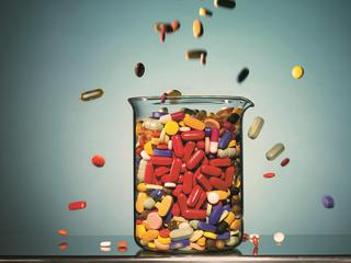 Pills Falling Into a Beaker