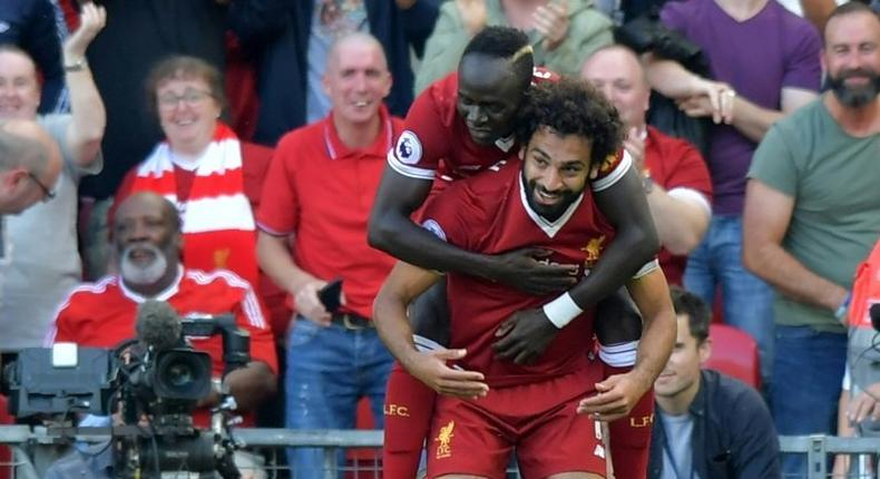 Liverpool's Mohamed Salah (R) celebrates with Sadio Mane after scoring their third goal during their match against Arsenal Liverpool, north west England on August 27