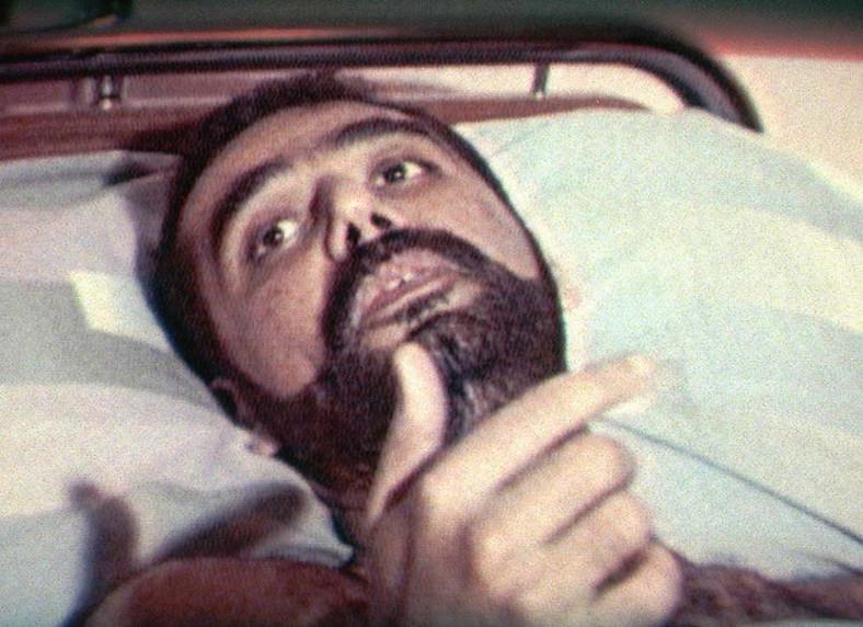 Zdjęcie z irackiej telewizji pokazuje 33-letniego Udajja Husajna, najstarszego syna Saddama Husajna, podczas wywiadu, którego udzielił z łóżka szpitalnego w Bagdadzie 2 stycznia 1997 r. Syn irackiego dyktatora, który przetrwał zamach na własne życie powiedział, że 4 tkwiące jeszcze w jego ciele pociski przynoszą mu zaszczyt