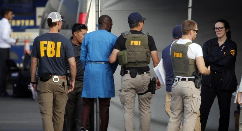 FBI agents holding one of the suspect arrested in the crack down on internet fraud