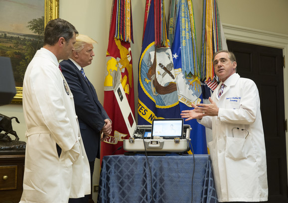 Sekretar Ministarstva za veterane dr Dejvid Šalkin (R) pokazuje opremu dr Roniju Džeksonu i predsedniku SAD Donaldu Trampu u Vašingtonu u avgustu 2017.