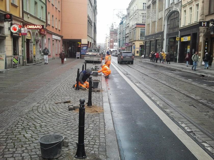 Robotnicy ustawiają słupki na chodniku przy ul. Ruskiej