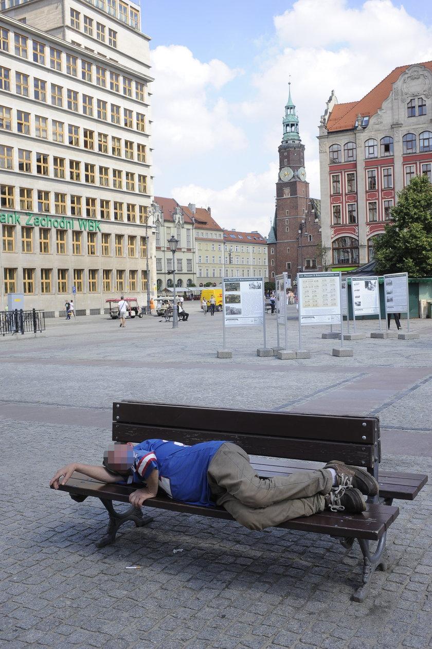 Bezdomny śpi na ławce na pl. Solnym