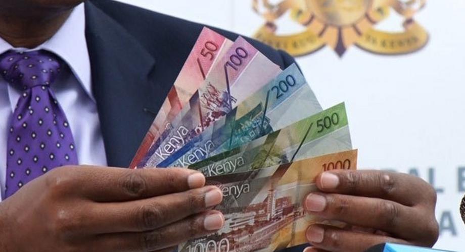 File image of CBK Governor Patrick Njoroge holding up Kenyan currency notes