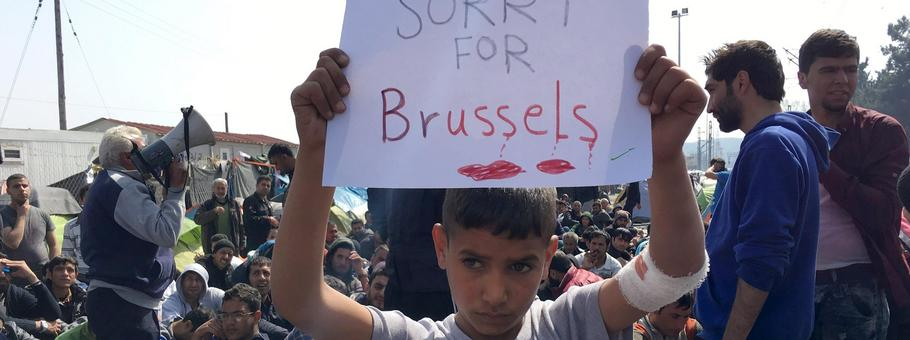 "A refugee boy holds up placard reading ""Sorry for Brussels"" as refugees and migrants take part in a"