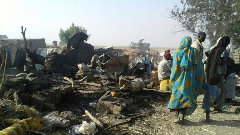 Survivors look at the aftermath of the bombing by the Nigerian air force of a camp for displaced people in Rann, northeast Nigeria, on January 17, 2017. (AFP)