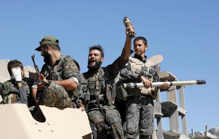 Fighters of Syrian Democratic Forces jubilate aboard an armoured fighting vehicle after Raqqa was li