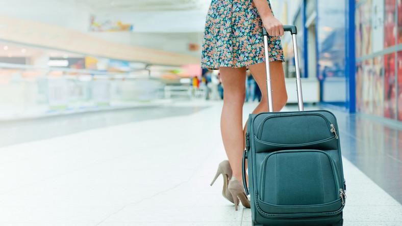 Kobieta z walizką na lotnisku w drodze na wakacje