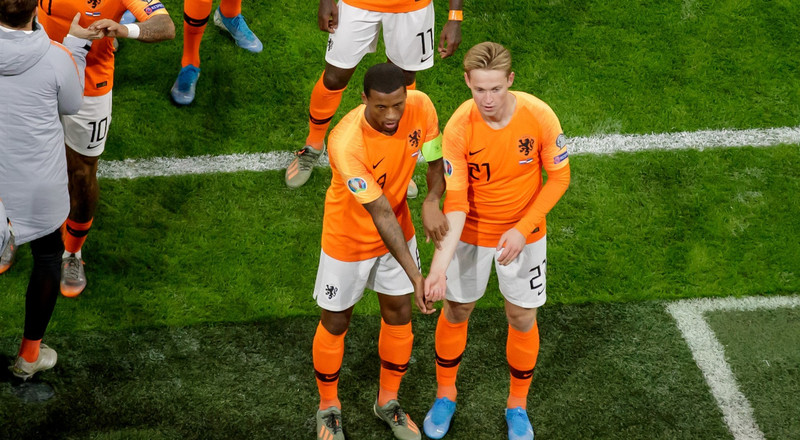 A black Dutch football player held his arm against his white teammate's in a powerful response to racial abuse in his home country