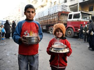Children carry cooked meals provided by the UN through a partner NGO at al-Mashatiyeh neighborhood o