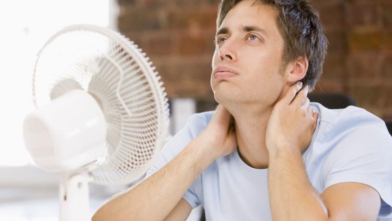 Mężczyzna chłodzi się przy wentylatorze