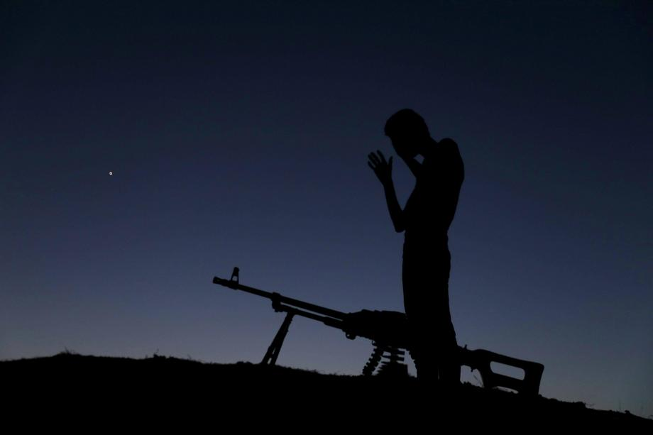 A Free Syrian Army fighter prays after eating his iftar (breaking fast) meal during the holy month o