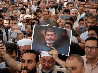 A man holds a picture of the former Egyptian president Mursi during a symbolic funeral prayer in Istanbul