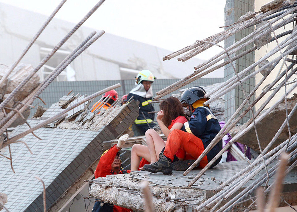 Rescue workers remove people from the site where a 17-storey apartment building collapsed after an earthquake hit Tainan