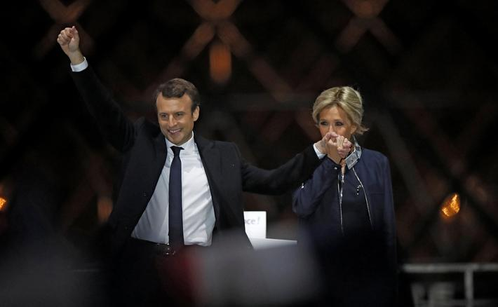 French President elect Emmanuel Macron and his wife Brigitte Trogneux celebrate on the stage at his