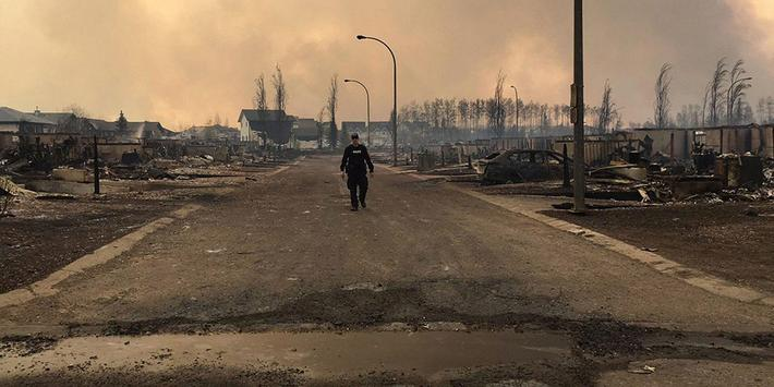 A Mountie surveys the damage on a street in Fort McMurray Alberta