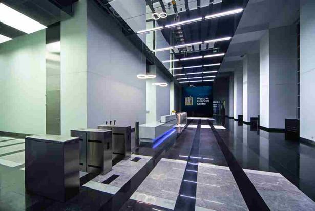 Inteligentne zarządzanie budynkiem zaczyna się od nowoczesnej aranżacji wnętrz. W odpowiedzi na potrzeby najemców i dynamicznie zmieniające się na stołecznym rynku nieruchomości komercyjnych warunki właściciele Warsaw Financial Center – Tristan Capital Partners i Allianz Real Estate systematycznie wprowadzają zmiany w swoim budynku. Położone przy ul. Emilii Plater Warszawskie Centrum Warsaw Financial Center – WFC może poszczycić się imponującym lobby, które nawiązuje do najwyższej klasy obiektów biznesowych na świecie, tworząc komfortową przestrzeń dla najemców i ich kontrahentów. W zaprojektowanej przez firmę Epstein przestrzeni dominują elementy czarno-białe, które doskonale współgrają z lustrzanym sufitem, nowoczesnym systemem oświetlenia i szklanymi panelami na ścianach przełamanymi akcentami ze stali szlachetnej. Uwagę gości zwraca jednak przede wszystkim imponująca ściana wizyjna złożona z 24 55-calowych monitorów. To jedyna ogólnodostępna konstrukcja tego typu w Polsce. Prezentowane są na niej treści związane bezpośrednio z budynkiem i wydarzeniami, które się w nim odbywają, oraz z Warszawą, w tym prace znanych polskich artystów. To bardzo ważne, ponieważ codziennie przez lobby Warsaw Financial Center przewija się prawie 4 tys. osób. To więcej niż wynosi średnia dzienna widownia w przeciętnym warszawskim kinie. W WFC wprowadzono też wiele innowacyjnych rozwiązań z myślą o komforcie pracy najemców i odwiedzających ich gości.