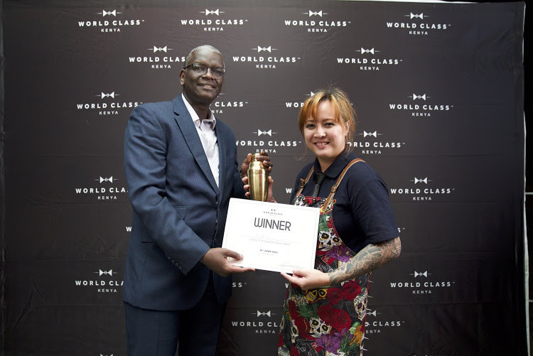 EABL sales director Andrew Kilonzo hands the World Class Bartender of the Year award to Angeliqua. (The Star)