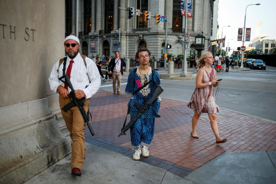 A woman walks past Micah Naziri and Jaimes Campbell, advocates for open carry, as they patrol the st