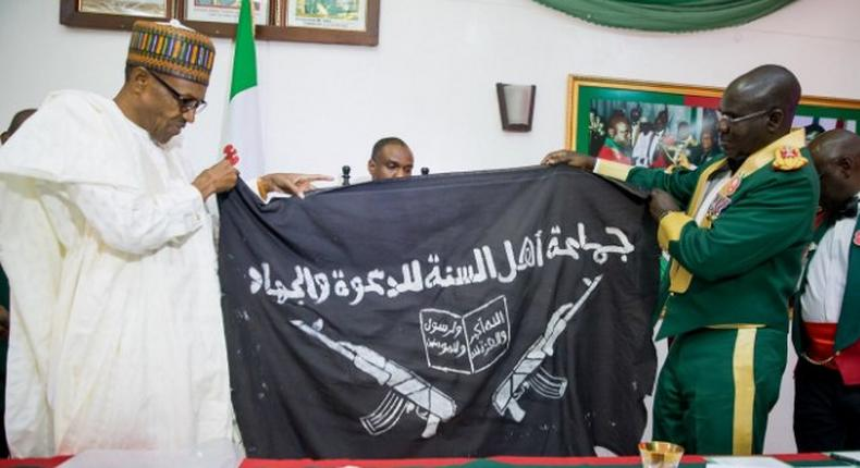 Army presents captured Boko Haram flag to President Muhammadu Buhari