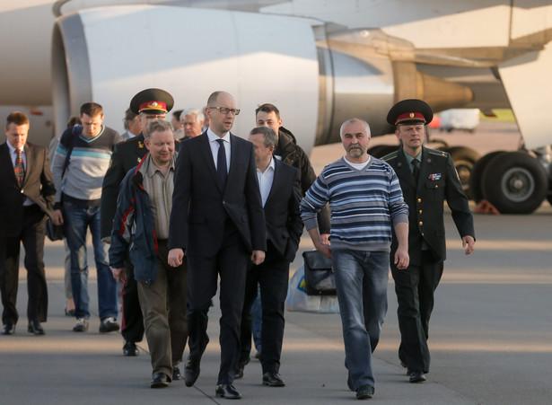 Arsenij JAceniuk i uwolnieni obserwatorzy OBWE na lotnisku w Kijowie. Fot. EPA/SERGEY DOLZHENKO