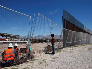 File photo of a boy looking at U.S. workers building a section of the U.S.-Mexico border wall at Sun