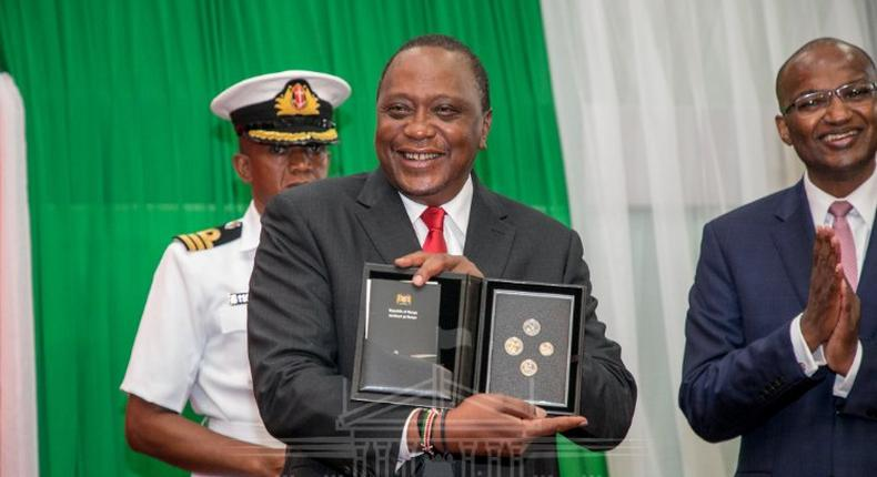 President Uhuru Kenyatta displays a set of the new currency Kenyan coins during their launch in December 2018 (PSCU)