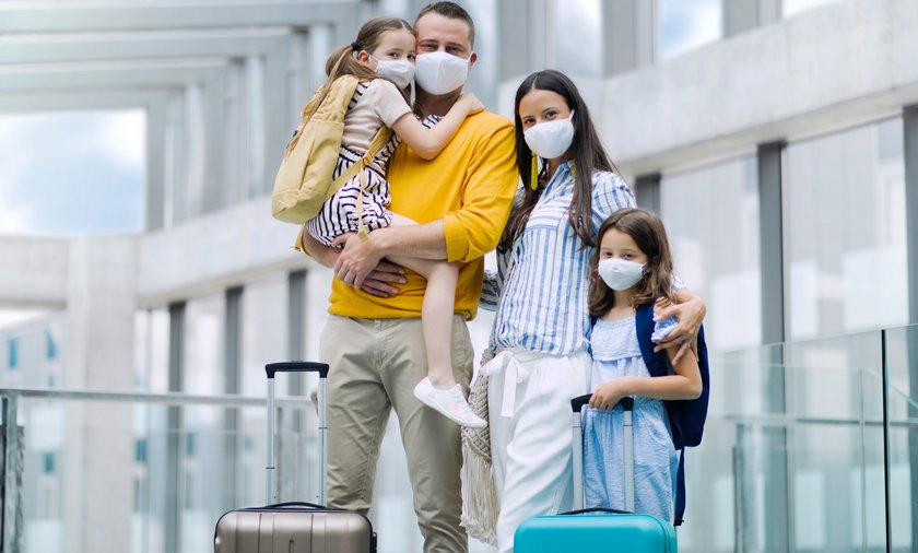 Family with two children going on holiday, wearing face masks at the airport.