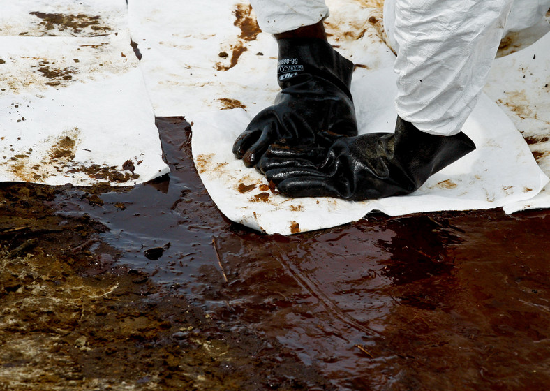 Katastrofa w Zatoce Meksykańskiej: Grand Isle, Louisiana, USA. Pracownicy zatrudnieni przez koncern BP przy użyciu wchłaniających ropę szmat czyszczą plażę z resztek czarnej mazi. Foto: Derick E. Hingle/Bloomberg