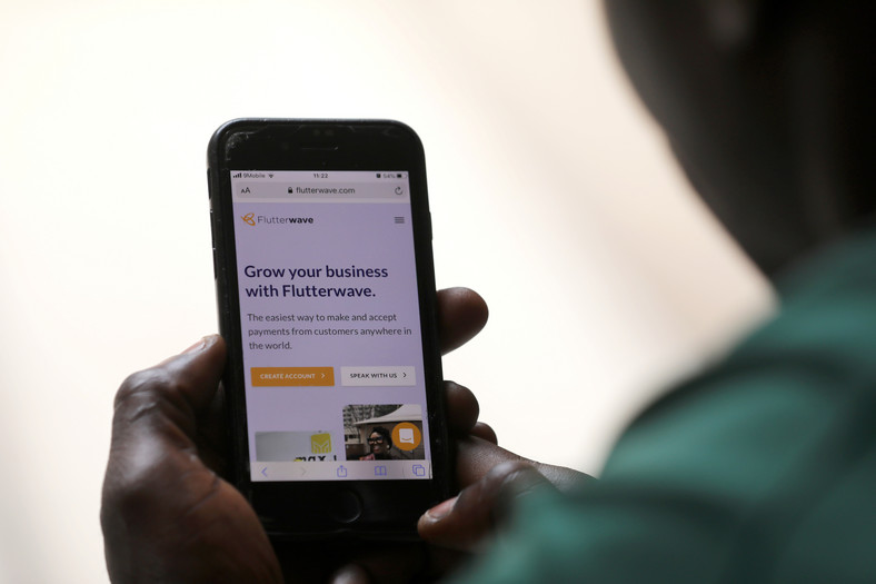 A man poses as he displays the Flutterwave homepage on a mobile phone screen in Abuja, Nigeria January 21, 2020. REUTERS/Afolabi Sotunde