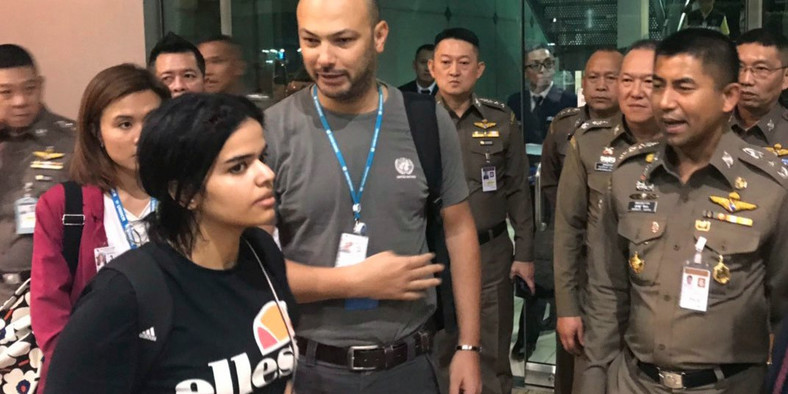 In this photo released by the Immigration Bureau, Saudi woman Rahaf Mohammed Alqunun, foreground walks by Chief of Immigration Police Maj. Gen. Surachate Hakparn, right, before leaving the Suvarnabhumi Airport in Bangkok