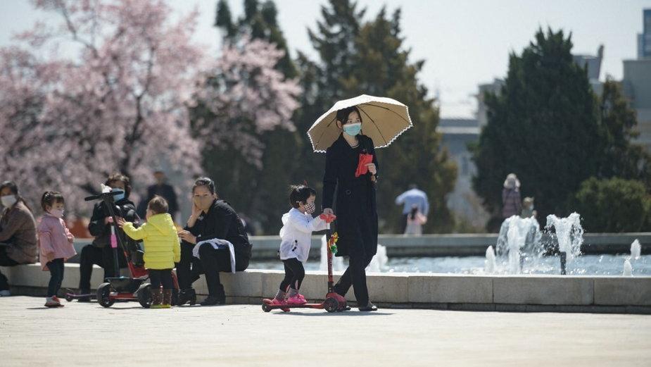 Kobieta z dzieckiem spaceruje przed fontanną w parku obok Wielkiego Domu Studiów Ludowych w Pjongjangu, 5 kwietnia 2021 r.