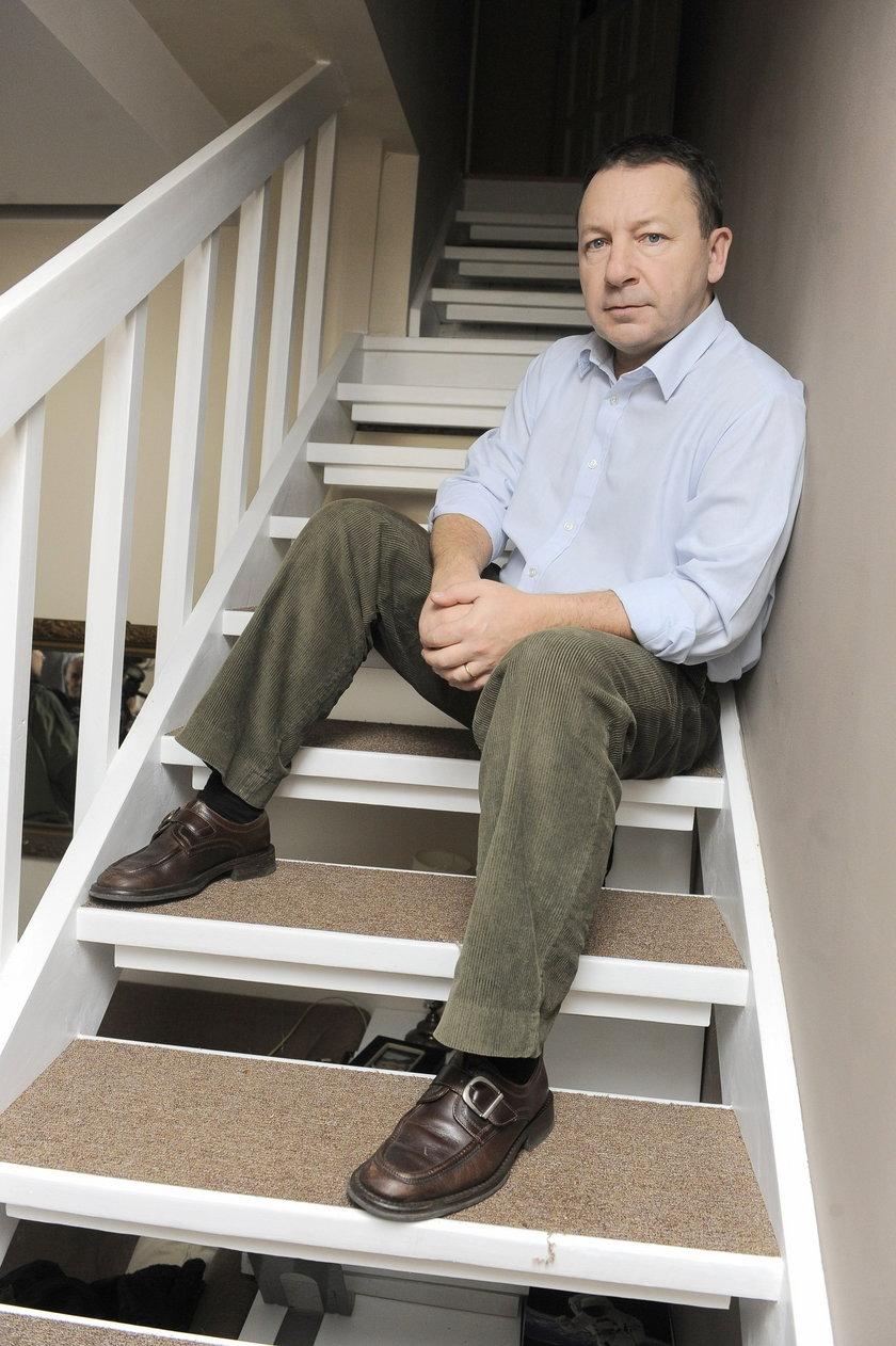 Zbigniew Zamachowski pozuje do zdjęcia na schodach