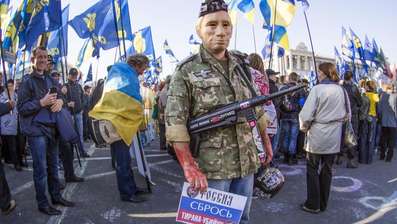 Mężczyzna w masce Władimira Putina, z pistoletem maszynowym i krwią na dłoniach na demonstracji w Kijowie