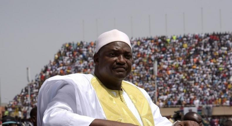 Gambian President Adama Barrow looks at the audience from the roof of a car as he arrives at the Independence Stadium in Bakau, west of the capital Banjul for his inauguration ceremony, on February 18, 2017