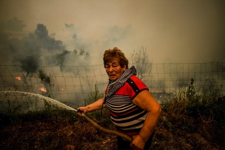 A villager uses a water hose to put out flames during a wildfire in the village of Roda, central Portugal, on July 21