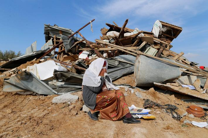 An Arab Israeli woman sits next to ruins from her dwellings which were demolished by Israeli bulldoz