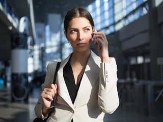 Concentrated woman talking on phone in office