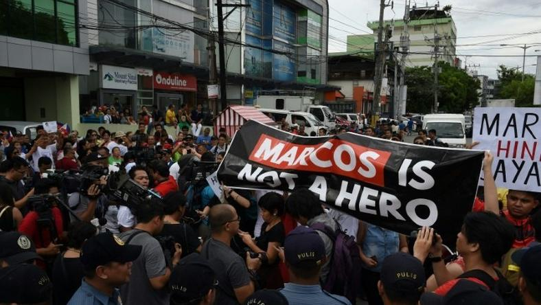 Anti-Marcos protesters (R) face off with pro-Marcos supporters (L) waving miniature national flags while the late dictator Ferdinand Marcos was being given a hero's burial in Manila on November 18, 2016