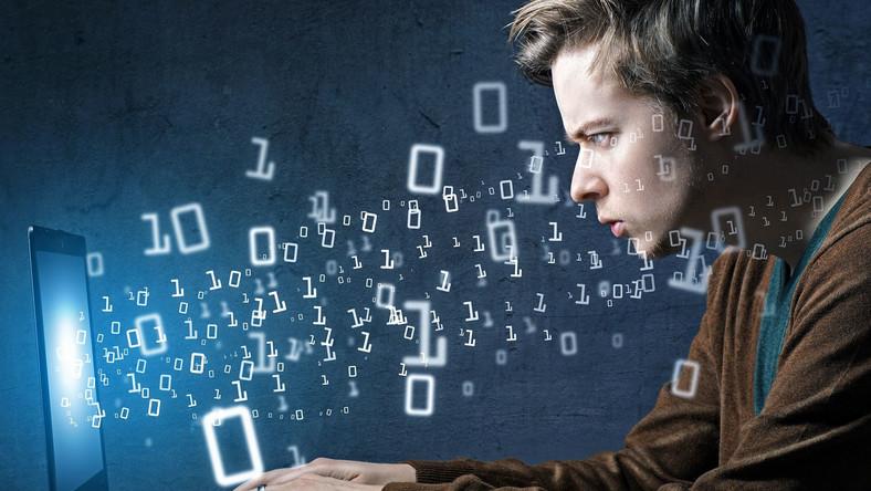 Mężczyzna korzystajcy z komputera w otoczeniu zer i jedynek