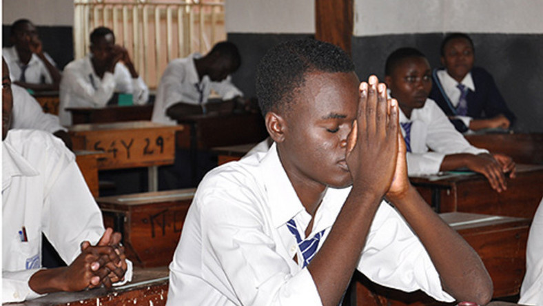 A student praying in an examination room