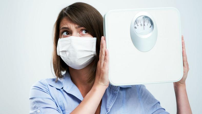 Kobieta w maseczce trzyma wagę; pandemia koronawirusa