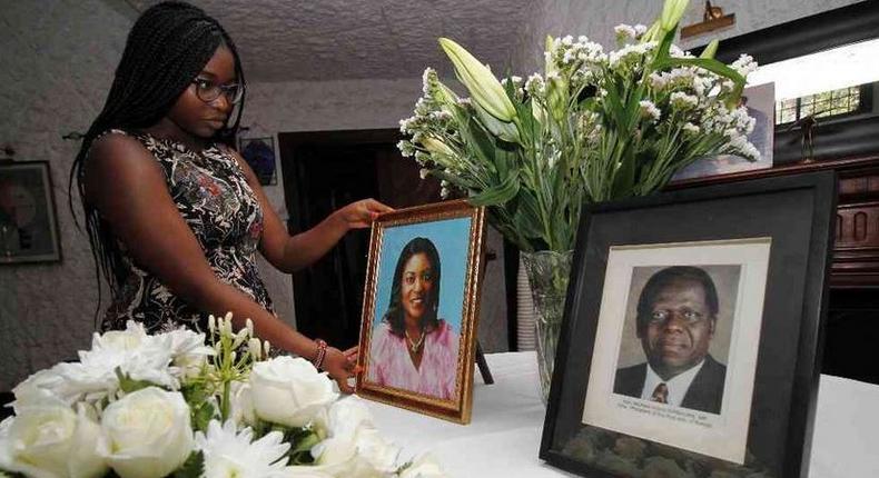 Chichi Wamalwa holding portraits of Yvonne and father Kijana Wamalwa at their Karen home