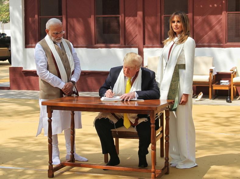 ... W kontekście wizyty media jak zwykle poddają ocenie wygląd pierwsze damy Stanów Zjednoczonych. Tym razem Melania jest wyjątkowo chwalona za stylizację, w której wysiadła z samolotu i brała udział w pierwszych spotkaniach. Biały kombinezon nie tylko doskonale podkreśla jej nienaganną figurę, ale także - dzięki szarfie zdobiącej pas i szerokim nogawkom - nawiązuje stylem do tradycyjnych strojów hinduskich...