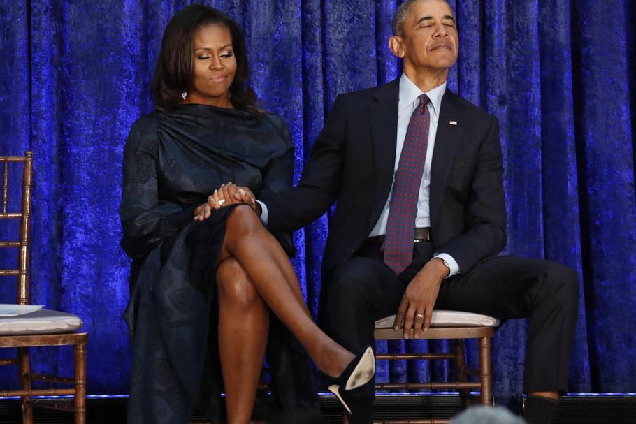 Former U.S. President Obama and first lady Michelle Obama hold hands prior to portraits unveiling at