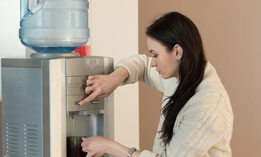 Kobieta pijąca wodę z dystrybutora